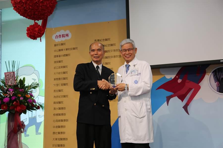 攝護腺癌病友林先生(左)贈送感謝獎座給童綜合醫院副院長歐宴泉。(王文吉攝)