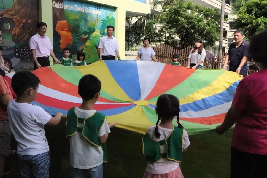 張明文現場和小朋友玩起氣球傘。(吳亮賢攝)