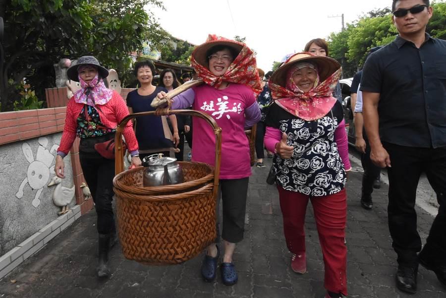 彰化縣長王惠美(右2)親自一肩扛起扁擔,為參與夏令營的學童們送上茶水點心,專業標準的架式讓一旁的農家婦女都稱讚。(謝瓊雲攝)