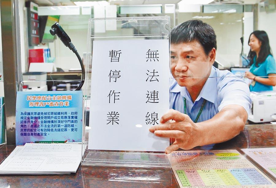 圖為郵局工作人員昨在櫃台貼出「無法連線,暫停作業」公告。(姚志平攝)