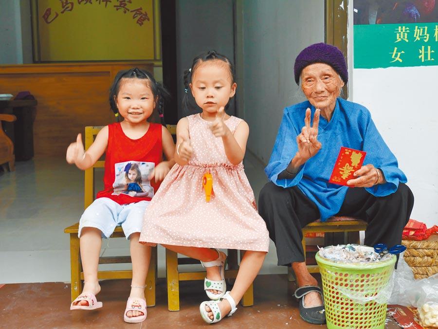 今年滿100歲的廣西巴馬人瑞黃媽桃,與曾孫女開心合影。(記者陳君碩攝)