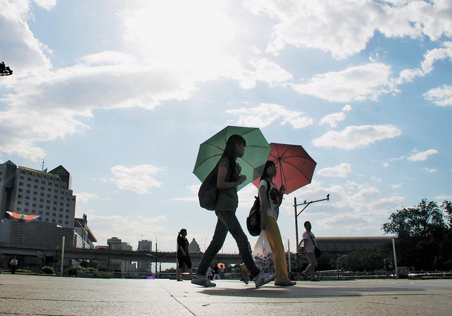 北京持續攝氏30度以上的高溫,展覽館廣場上,2位市民正用遮陽傘遮擋紫外線。(中新社資料照片)