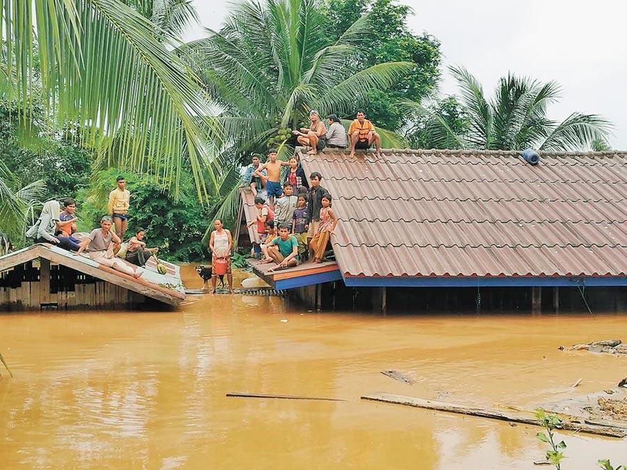 2018年7月24日,寮國阿速坡,居民在屋頂躲避潰壩事故帶來的洪水。(新華社)