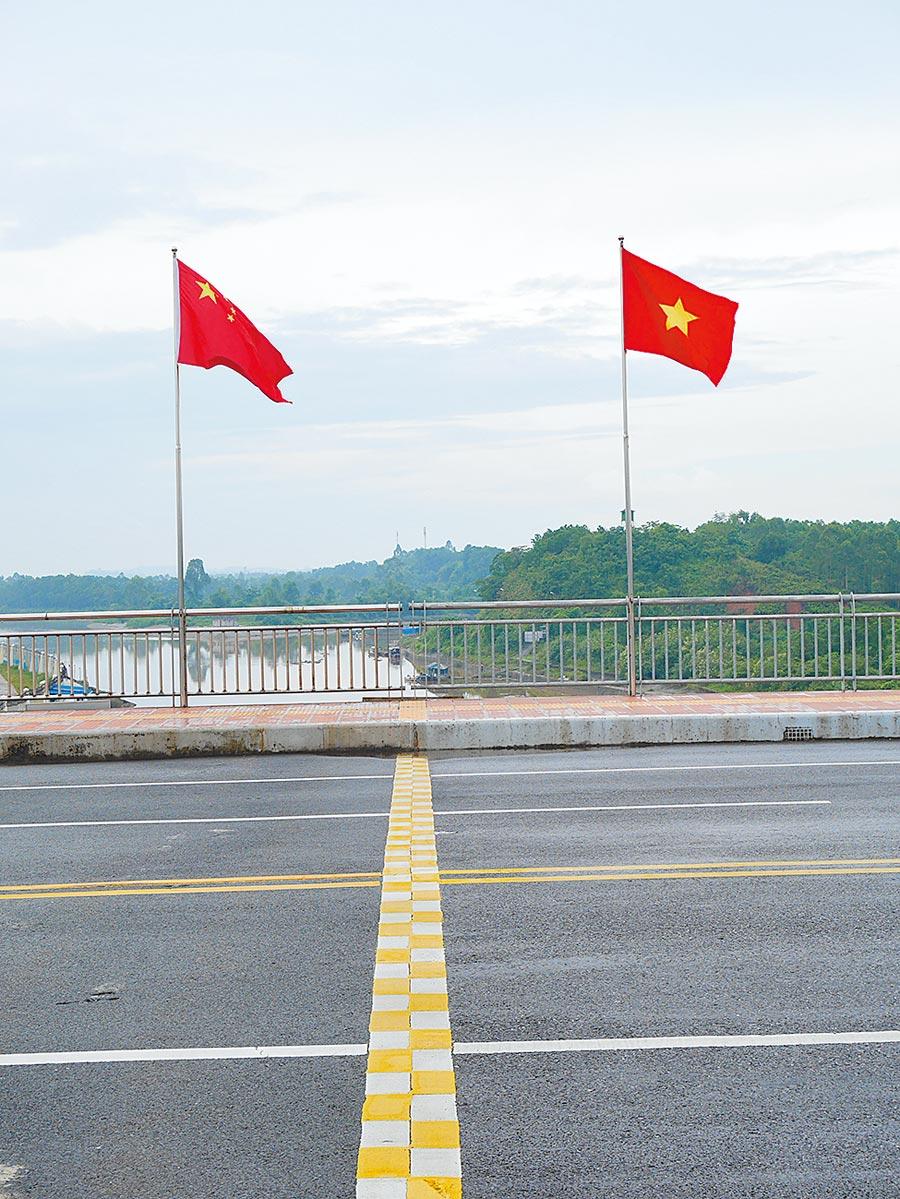 廣西東興口岸與越南交界處,插有兩國國旗。(記者陳君碩攝)