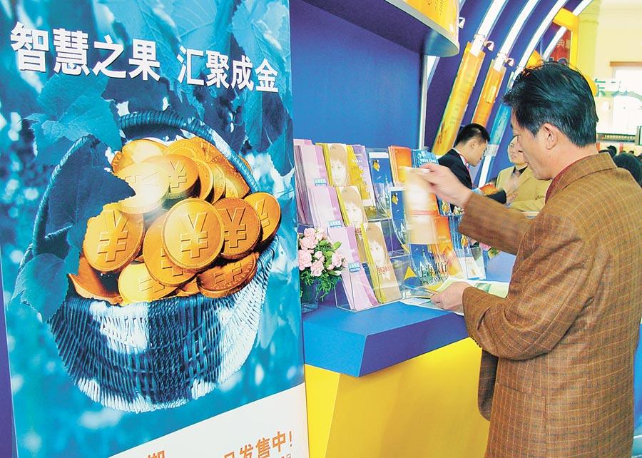 上海理財博覽會上一市民在取銀行的理財產品資料。(CFP)