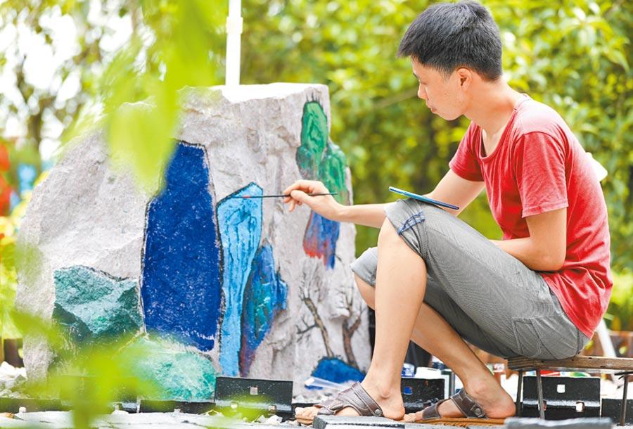 陳陽正在道砟石上繪畫。圖/章娜