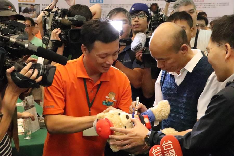 韓國瑜出席三重北漂就博會,熱情粉絲拿娃娃給韓國瑜簽名。(吳亮賢攝)