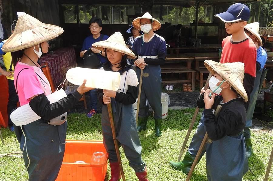 「一日農夫」社區體驗,由一新里導覽解說員向學員說明要觀察記錄台灣白魚,須先學會蝦籠的擺放位置。(楊樹煌攝)