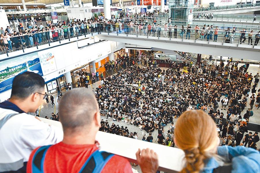 抗議人士26日在香港國際機場接機大廳集會反對有爭議的《逃犯條例》,圖為從高架通道俯瞰群眾。(法新社)