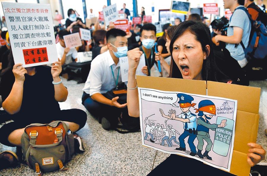 群眾舉牌抗議元朗暴力事件。(路透)