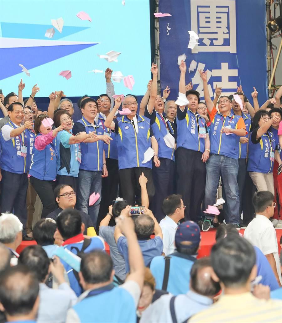 中國國民黨第20屆第3次全國代表大會28日在新北市板橋體育館舉行,閉幕時,黨主席吳敦義(中)與所有台上人員一起擲出紙飛機,象徵要讓國民黨團結、向上起飛。(劉宗龍攝)