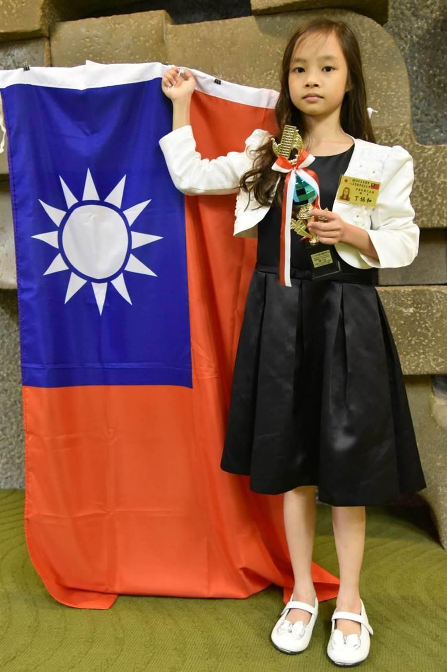 我心算神童丁協和勇奪世界大賽冠軍,賽後在會場秀出國旗與獎盃留影。(柯宗緯翻攝)