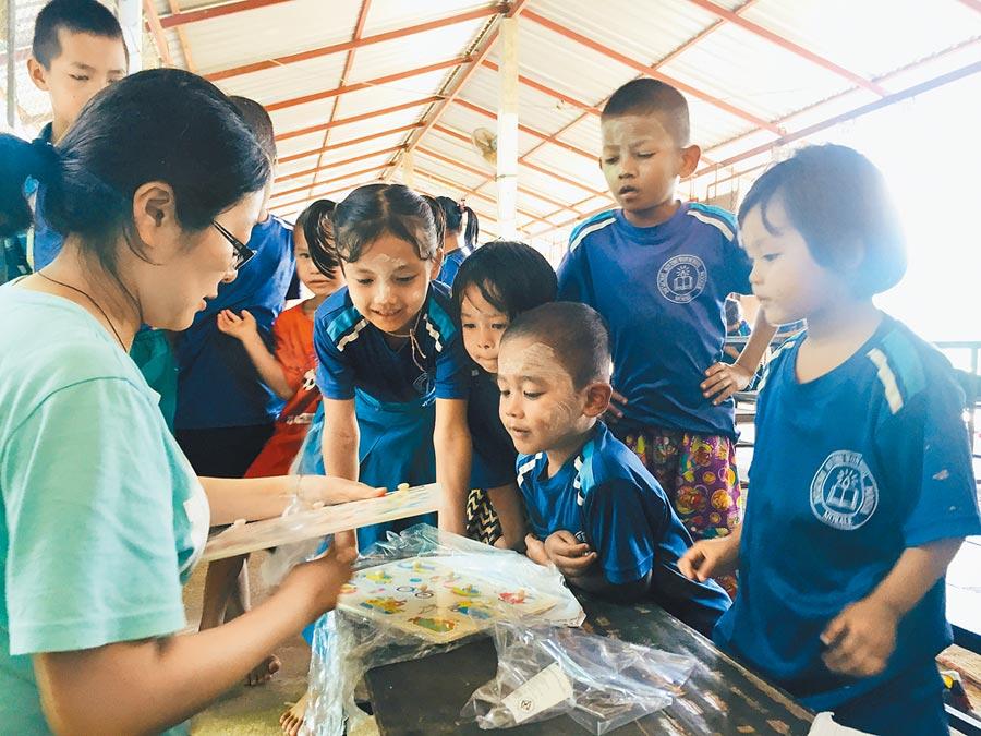 泰緬邊境部落學校師資不足,大多時候一個老師負責20至70位學生。吳佩璇(左一)正發送學齡用具,減輕教師負擔。(教育部提供)