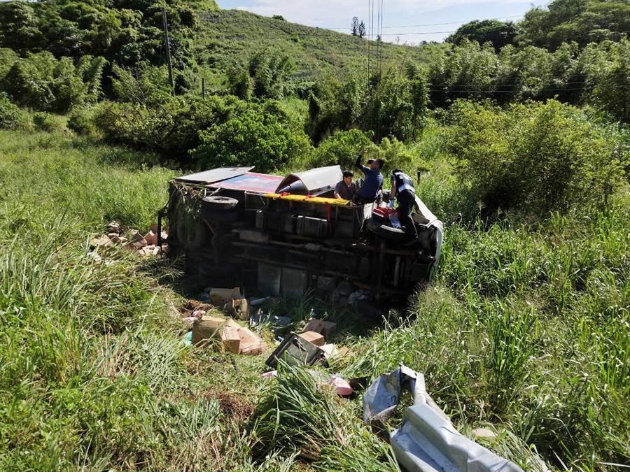 小貨車翻落10米深的國道邊坡,司機受困車內,消防人員現場搶救。(洪榮志翻攝)