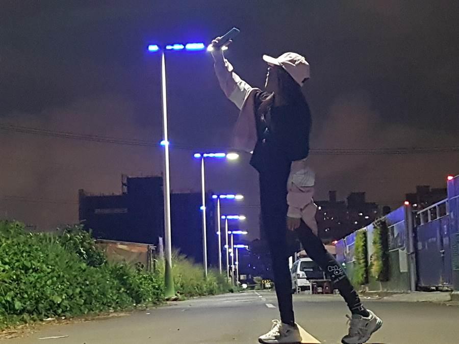 幽藍色的路燈點亮,無人街道且整排「藍光點點」,讓人有種「寂寞藍色街道」感覺,正值暑假期間,很多學生朝聖拍照打卡。(張妍溱攝)