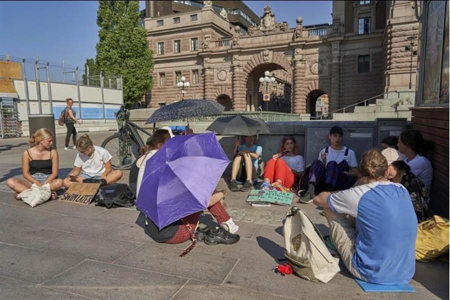 一群倡議透過行動對抗暖化的學生,26日坐在瑞典首都斯德哥爾摩的國會門口。在烈日下,他們也忍不住撐起陽傘。(美聯社)