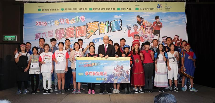 國泰學童圓夢計畫成果發表會,董事長錢復(中)與獲選小朋友們合影。(國泰金提供)