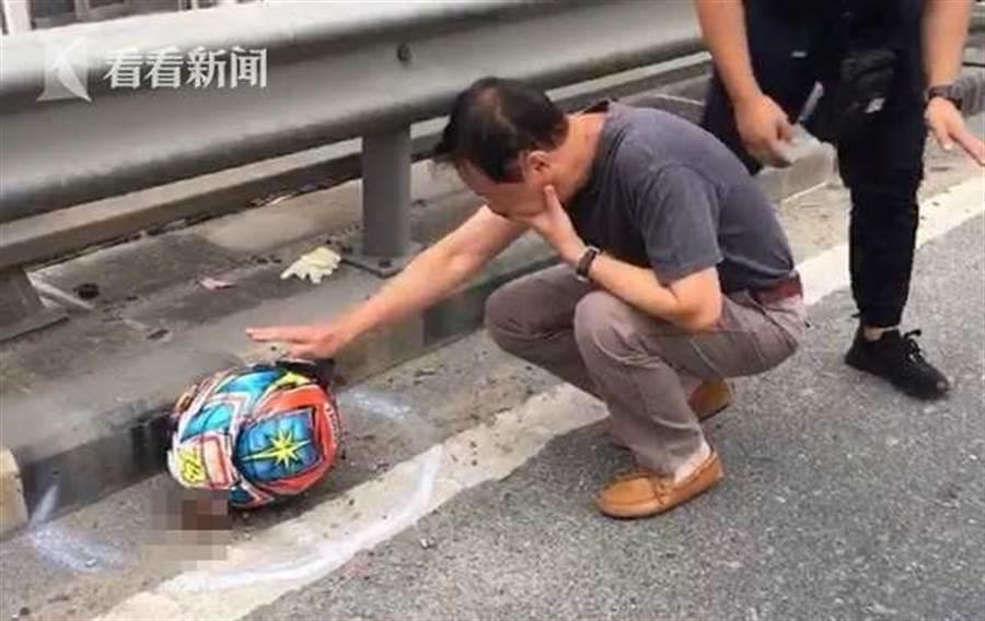 死者父親崩潰的蹲在地上,難過的撫摸死者的頭盔,久久不願放手。(翻攝自看看新聞)