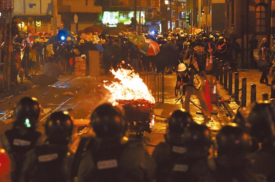 7月28日晚上8時許,示威者在警方防線前,點燃紙皮等雜物縱火。(中新社)
