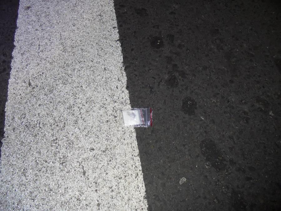 熱心民眾向警方指稱看見李姓駕駛打開車窗丟棄物品,警方前往查看,發現是一包白色粉末及針筒,李嫌藏毒事跡敗露。(盧金足翻攝)