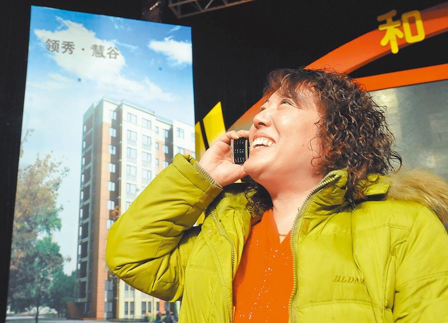 房市限價搖號背離市場經濟。圖為2010年3月1日,北京限價房首次搖號配售,中籤的民眾跟家人報喜。(新華社)