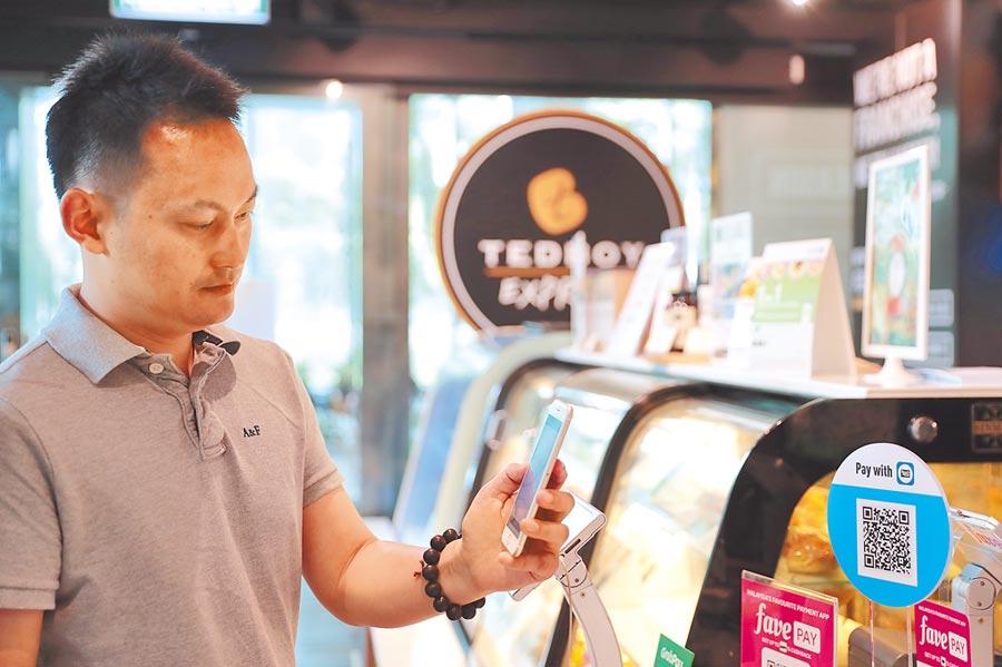馬來西亞吉隆坡,一名男士用支付寶買咖啡。(新華社資料照片)