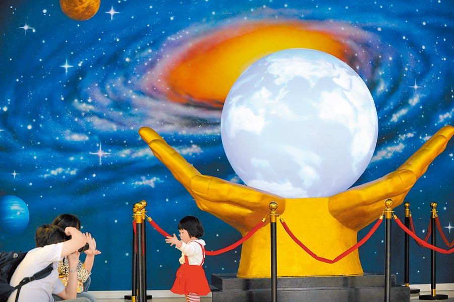 市民帶著孩子在南京科技館參觀「宇宙中的地球」。(新華社資料照片)