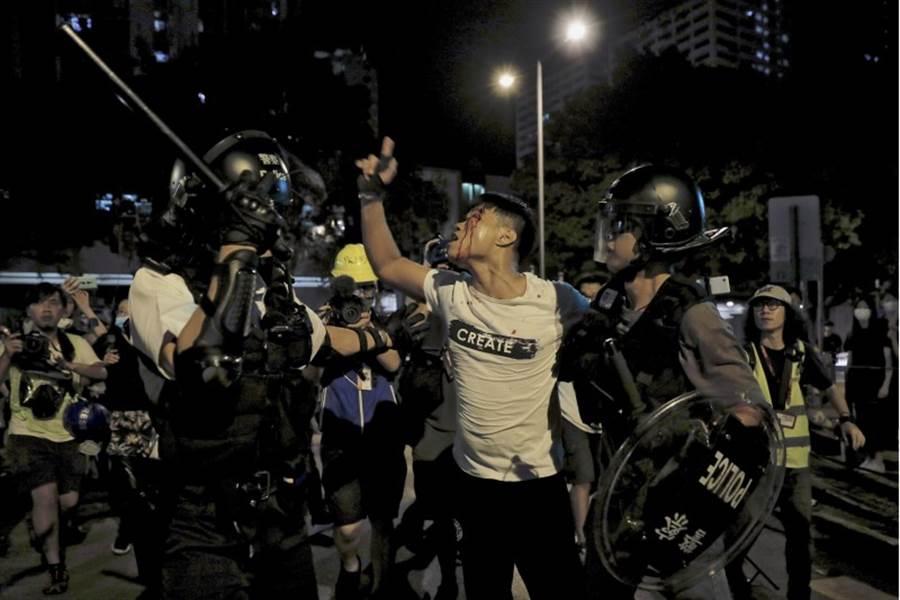香港30日晚間接連發生2起抗議人士包圍警署的示威行動,葵涌警署、天水圍警署分別遭到近千人包圍。圖為葵涌警署外,一名白衣男子與現場抗議人士發生衝突後,被打到頭破血流、遭警方帶走的畫面。(美聯社)