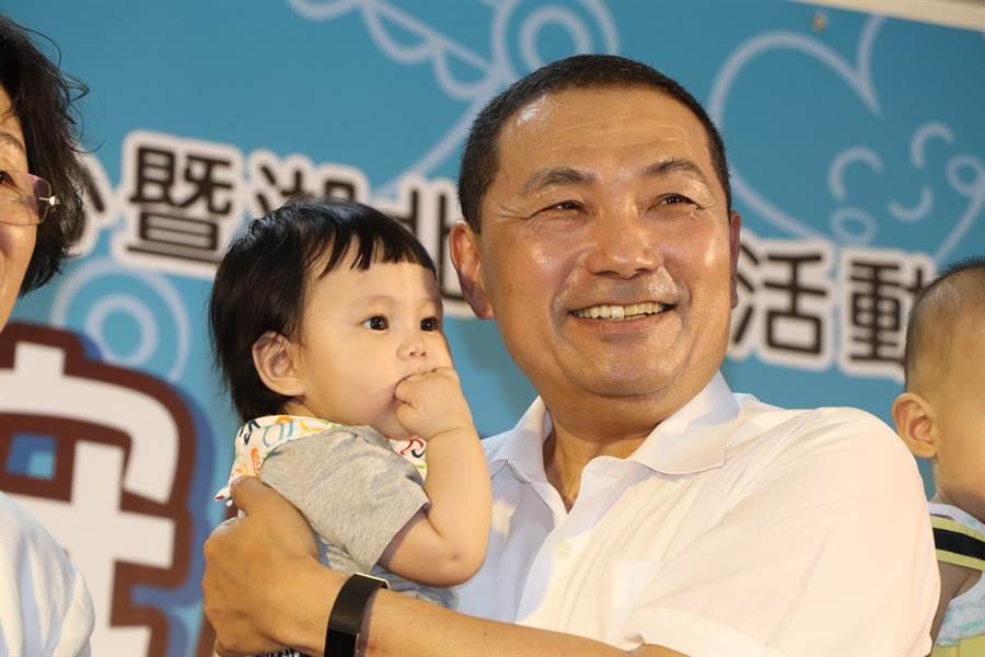 新北市長侯友宜親自到場主持,開心抱著可愛的公托學童。(吳亮賢攝)
