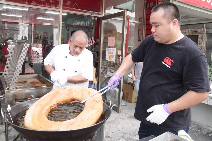 小米甜甜圈師傅麥順英(左)捐製直徑30公分巨無霸小米甜甜圈。(陳淑芬攝)
