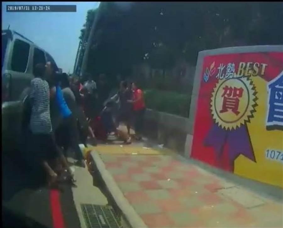 路人合力抬車協助女童脫困。(陳淑娥翻攝)