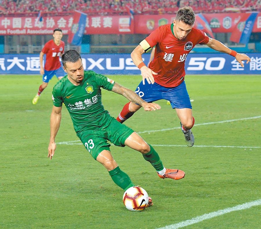 7月27日中超聯賽第20輪比賽中,北京中赫國安隊球員李可(左)與河南建業隊球員伊沃在比賽中拚搶。(新華社)