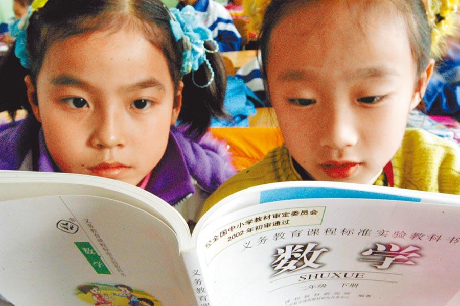 新疆一小學的兩名學生正在翻閱數學課本。(新華社資料照片)