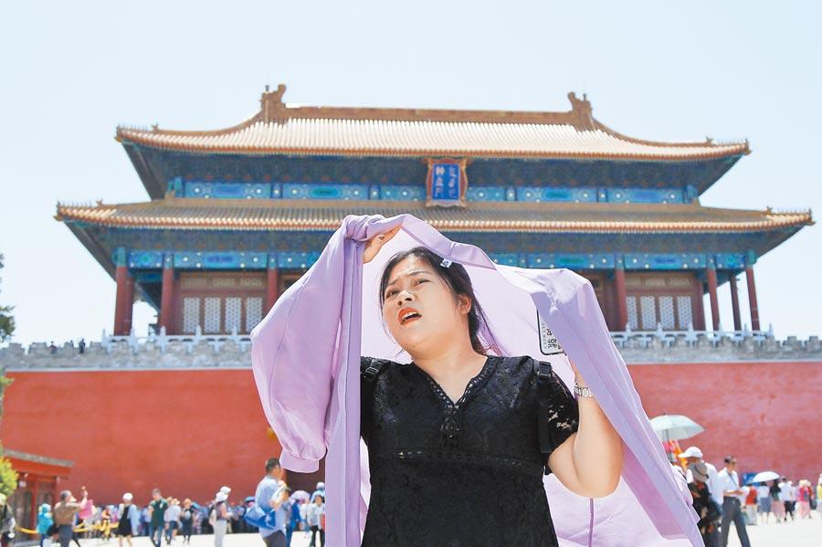 北京一名遊客將衣物披在頭上遮陽。(中新社資料照片)