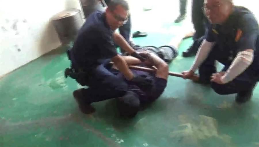 嫌犯受傷後,還爬到隔壁民宅頂樓,和圍捕警方對峙,擲菜刀、丟鐵條反抗,最後被優勢警力給制伏。(吳敏菁翻攝)