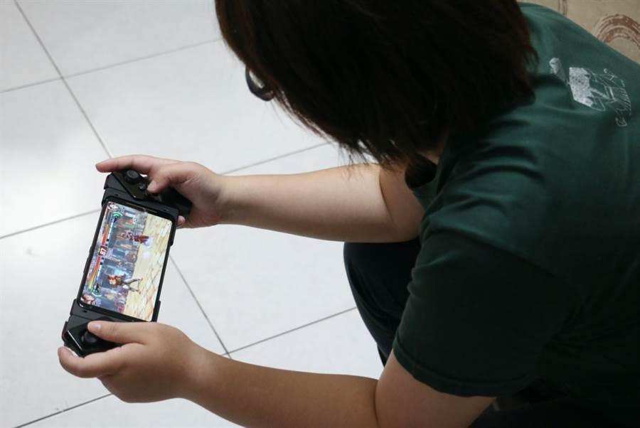 ROG Phone II搭配Kunai GamePad遊戲控制器玩遊戲。(圖/黃慧雯攝)