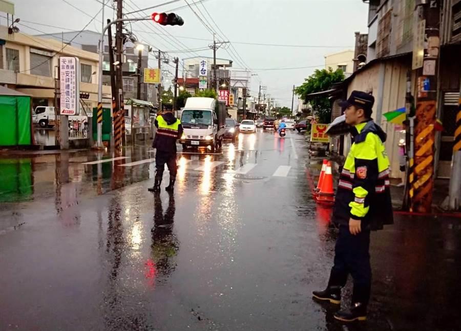 大雷雨造成高雄市湖內區和平路與仁愛街口一度傳出積水現象,員警趕抵現場指揮交通,所幸傍晚水已退去。(袁庭堯翻攝)