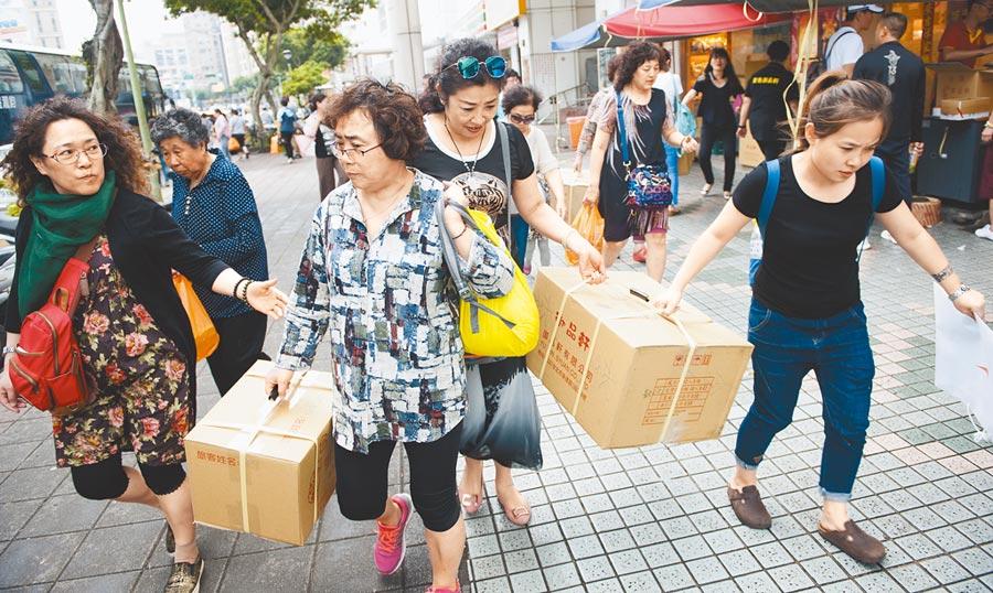 大陸自8月1日起暫停核發台灣自由行的申請,衝擊台灣觀光業。圖為來台旅遊的陸客,在特產店購物後打包,準備帶回家鄉。(本報資料照片)