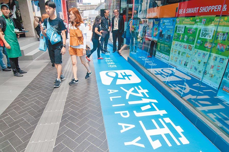 在馬來西亞吉隆坡,人們從一家提供支付寶行動支付服務的商鋪旁走過。(新華社資料照片)