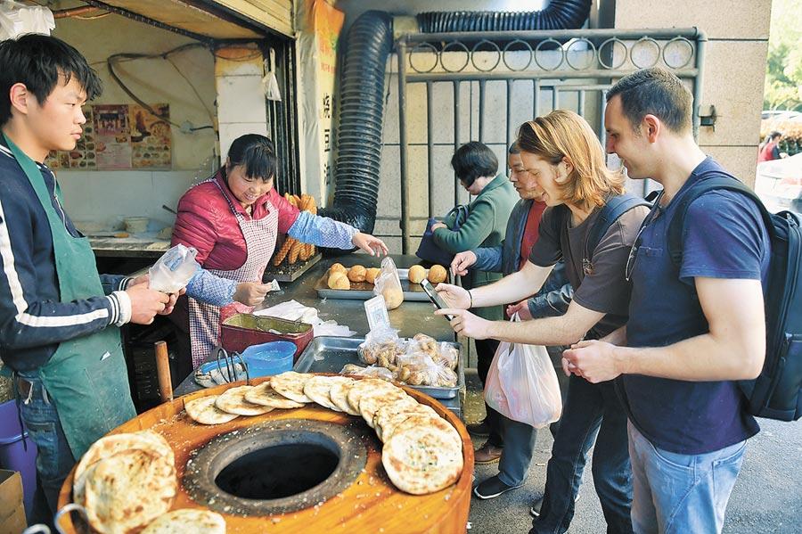外國人體驗行動支付。在杭州街邊一家小吃店,兩名外國朋友使用手機支付,購買燒餅當早餐。(新華社資料照片)