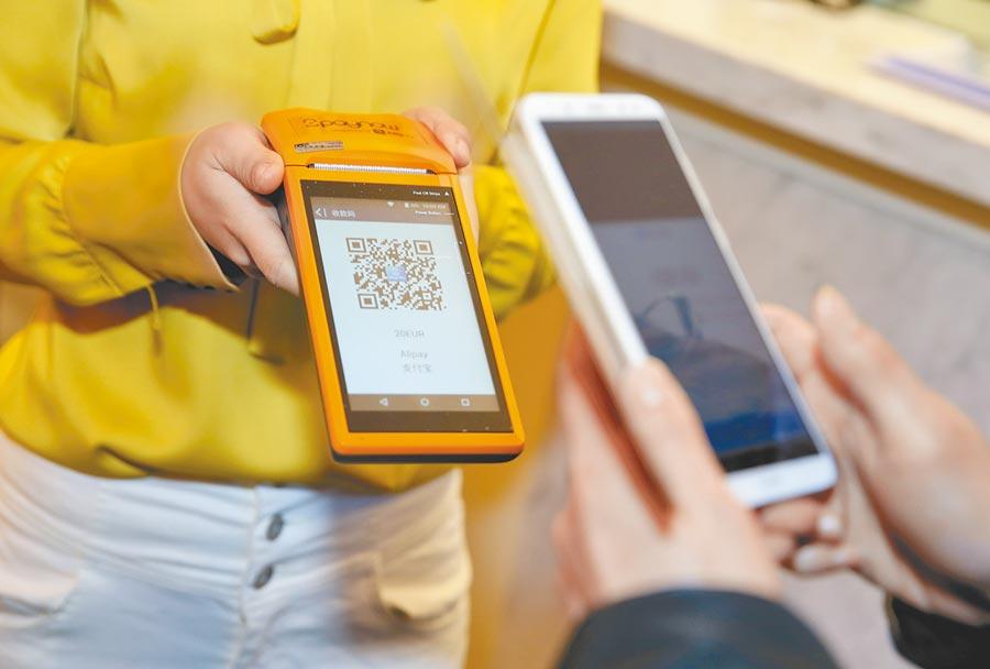 大陸駐比利時大使館推動行動支付領事收費服務,一名護照取證人完成掃碼付費程序。(新華社資料照片)