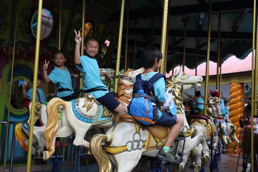 桃園市陳康國小學童到麗寶樂園進行「暑假遊記趣」,開心乘坐旋轉木馬。(王文吉攝)
