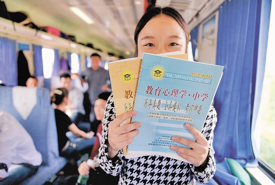 一名江西科技師範大學學生在車上K書,準備中小學教師資格證考試。(新華社)