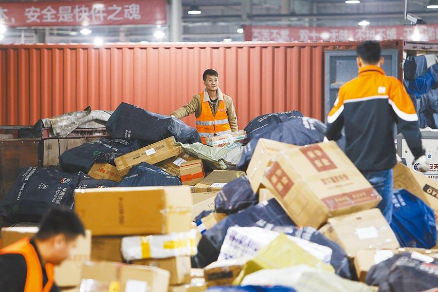 2018年11月11日晚,在申通快遞上海轉運中心,工作人員等待分揀完的商品裝車。(中新社)