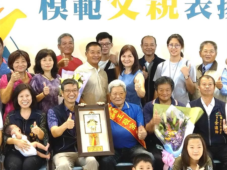 台中市環保局吳志超(左二)代表市長盧秀燕向模範父親致意,隨後偕同西屯區長陳寶雲(左一)頒獎給模範父親。(盧金足攝)