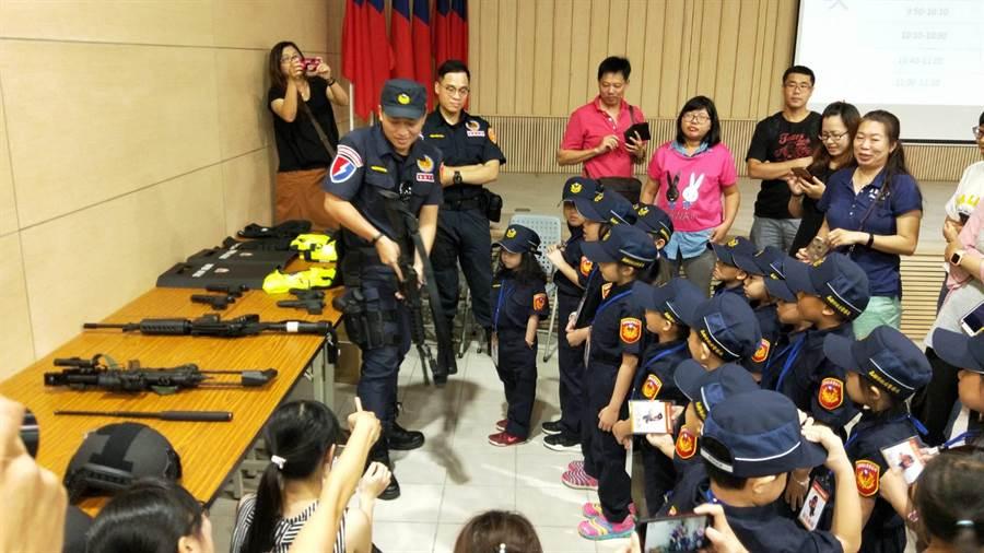 小小警察們經由員警介紹下,初步了解警用武器及裝備。(林雅惠翻攝)