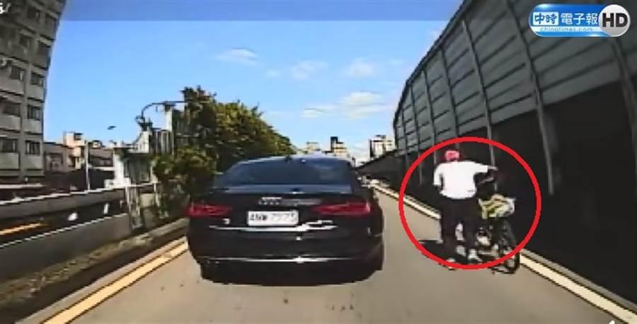 誤闖快速道路的老翁牽腳踏車緩慢前進、險象環生。(圖/取自《中時電子報》粉絲團)