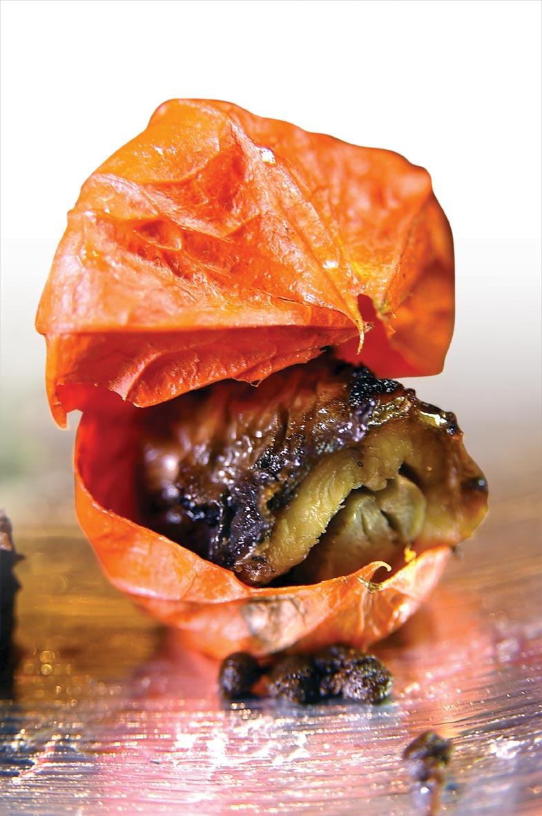 用錦燈籠花當容器盛裝的〈鰻魚八幡卷〉,是將鰻魚切片後與牛蒡綁在一起再烤製,這種料理技法源於明治維新前的京都八幡市。圖/姚舜