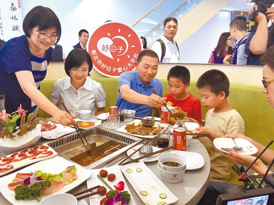 新北市長侯友宜與接受安置的兒童、少年一起吃火鍋,貼心幫他們挾菜。(王揚傑攝)