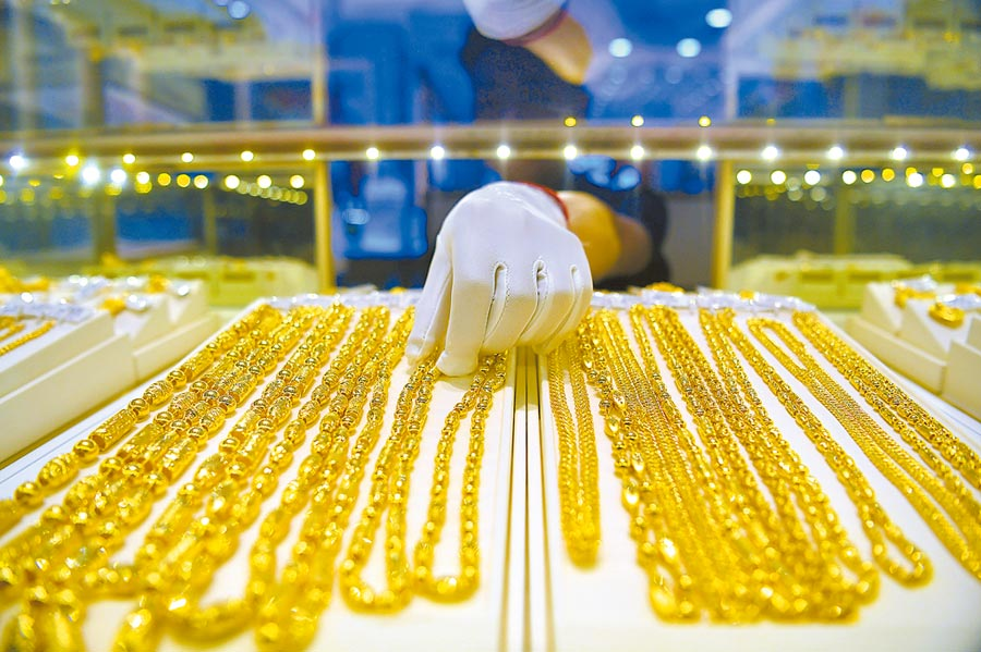 金價得天時地利,明年料上看1500美元。圖為重慶金店內工作人員正在整理黃金飾品。(中新社資料照片)